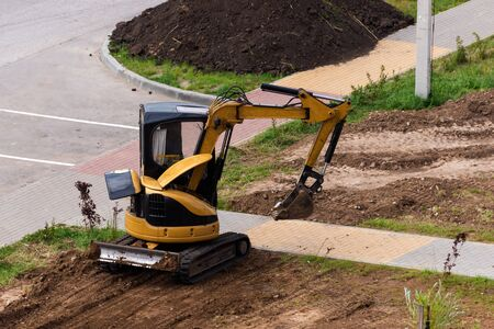 A small excavator rams the ground after replacing the pipes.Next to the sidewalk and the lawn. 写真素材