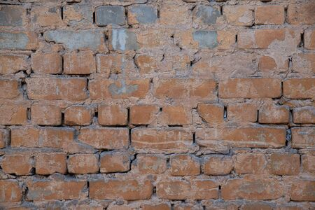 Texture of brick wall with peeling orange-and-gray paint