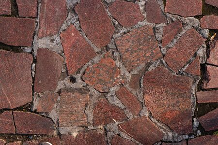 The texture of the sidewalk, from pieces of granite