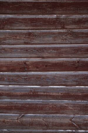 The texture of the old wall of wooden boards painted in Burgundy