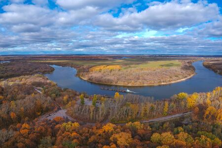 Aerial view: A large panorama of a barge floating on the river in autumn near the autumn forest . Ryazan forest Park in autumn Banco de Imagens