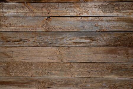 Texture of old wooden wall with peeling beige paint from boards