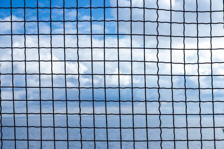 The sky and the sea behind bars