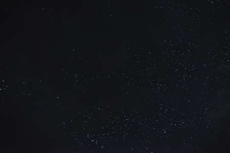 Stars in the night sky through the clouds on a summer night