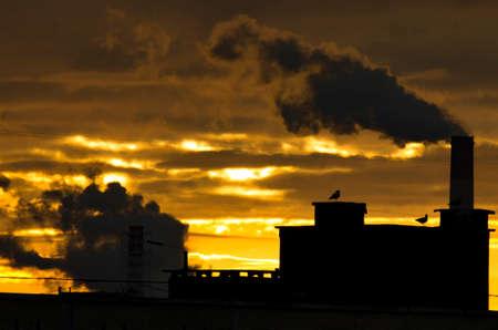 the rising sun: tuberías industriales de la ciudad de humo sobre el fondo de un sol naciente.