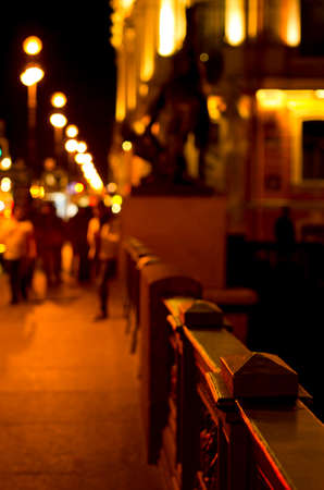 Part of the night street. People out of focus walk around the city.
