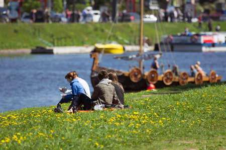 considers: The young couple considers the Vikings ship which has appeared on the river. The annual festival of the Norwegian Vikings which is taking place in May in St. Petersburg (Russia).