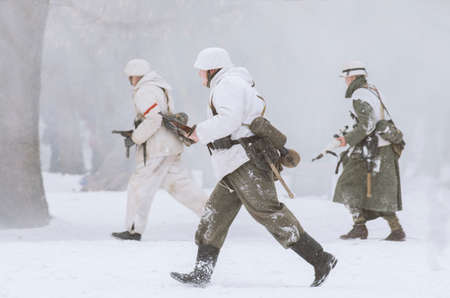 militant: The park Ekaterinhof, St. Petersburg (Russia) - February 23, 2017: Military historical reconstruction of events of World War II. German soldiers with weapons at the ready in the snowy haze fleeing the attack.