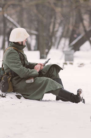 wehrmacht: The park Ekaterinhof, St. Petersburg (Russia) - February 23, 2017: Military historical reconstruction of events of World War II. A German soldier warming his hands in anticipation.