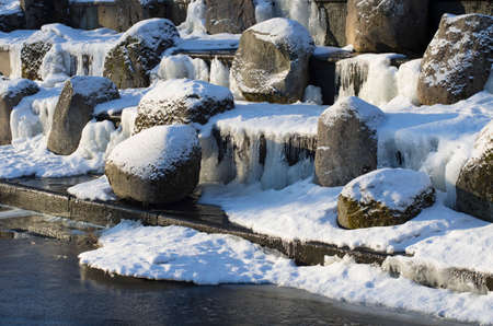 Snow-covered boulders on the granite cascade in icy system of ponds of Tsarskoye Selo(St.Petersburg).