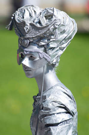 Saint Petersburg, Russia - June 4, 2017: VII international festival of street theaters Elagin Park. Living statue of a lady hiding behind the mask. Editorial