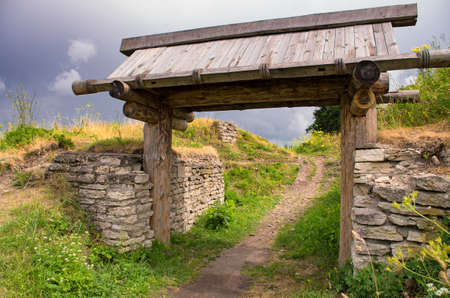 The wooden gate in the ancient Truvors settlement in cloudy weather (Pskov Oblast).