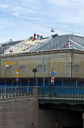 steeplejack: Builders assemble the roof of the building in the summer under the blue sky on the canal