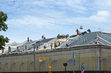 visible: Team builders does installation of a roof of the building in the summer under a blue sky Stock Photo