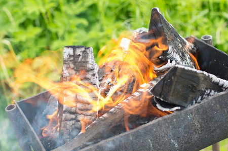 Smoky and blazing firewood in a brazier gradually turning into coals