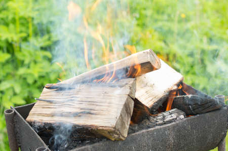 outdoor fireplace: Smoky firewood in a brazier gradually turning into coals