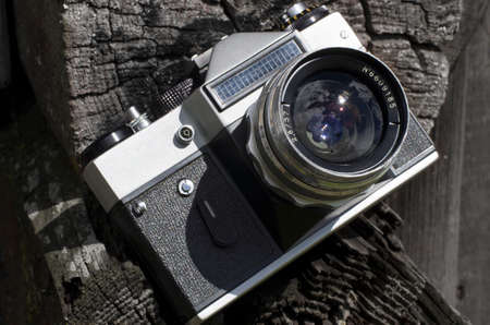 Vintage camera with a silver lens on a background of old logs