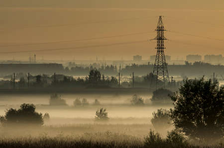 Fog over fields and tower of power lines on the outskirts of the city on the background of power lines Stock Photo
