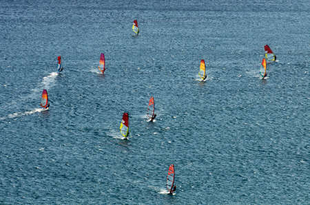 Many windsurfers on the sparkling waves of the Mediterranean sea at Cape Prasonisi (Greece) Stock Photo