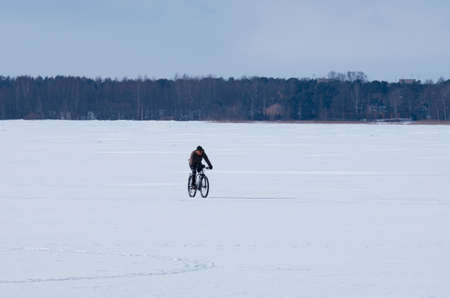 The lake Sestroretsky Razliv, St.Petersburg (Russia) - March 14, 2017: Male cyclist riding a bicycle in the winter barren landscape