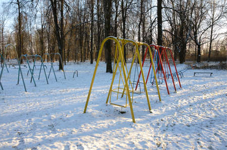 Swing at the deserted playground covered with snow in winter time