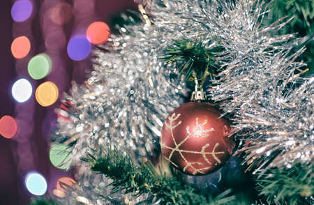 Red ball with snowflake on a Christmas tree in shiny tinsel with beautiful bokeh Archivio Fotografico
