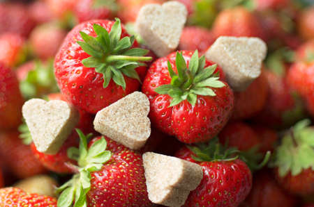 Juicy ripe berry red strawberry with chunks of cinnamon sugar in the shape of hearts