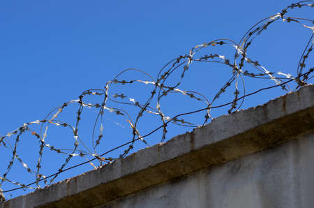 Coils of barbed wire with spikes over the concrete fence closeup Banque d'images - 108263612