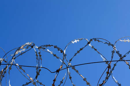Coils of barbed wire with spikes over the concrete fence closeup Stock Photo
