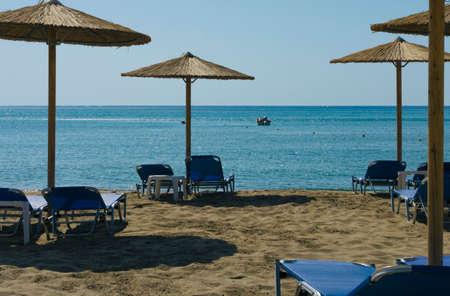 Mediterranean landscape with beach umbrellas and sunbeds in the background blue sky 写真素材