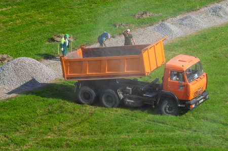 Saint Petersburg,Russia - June 20,2019: Dump truck KAMAZ poured gravel and raised clouds of dust and drives off. Working laborers with shovels.