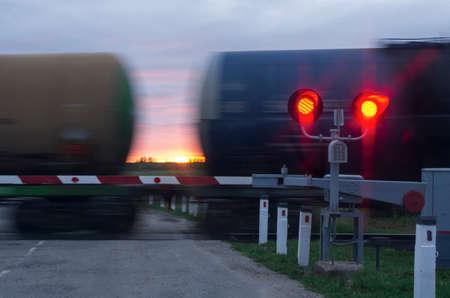 Deux feux de circulation avec feu rouge et barrière dans les wagons en mouvement et coucher de soleil Banque d'images