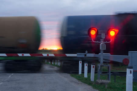 Two traffic lights with red light and barrier in the  moving wagons and sunset