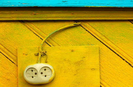 Old-fashioned electrical outlet with a cut-off wire on a yellow-blue wooden wall closeup Stock Photo