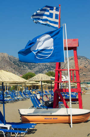 Flag of Greece and the Blue flag are flying over the rescue tower on the sandy beach of Crete and near the rescue boat