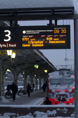 Vitebsky railway station,Saint Petersburg,Russia - January 24, 2019: Luminous scoreboard with the schedule of trains in Russian and duplication in English. In the background, the train covered with snow and the platform number 3.