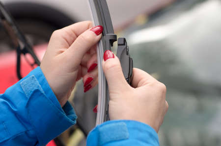 Young girl with red nails is preparing to put a new car windshield wiper brush to replace the old wiper blade