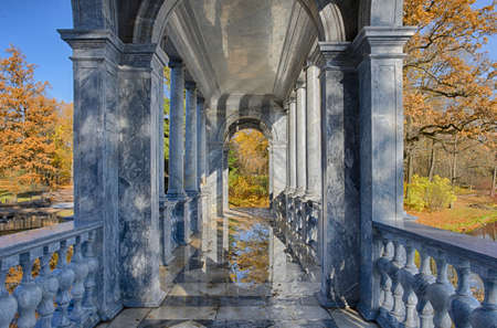 Autumn landscape with arcade of the Marble bridge with reflections of foliage in a puddle on the floor during the Indian summer (Saint Petersburg, Russia)