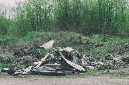 Pile of construction debris and waste near the spring young forest