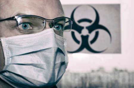 "Frightened look of a man in glasses with a surgical mask on his face in the background ""biohazard sign""(public use) and the silhouette of the city stylized film"