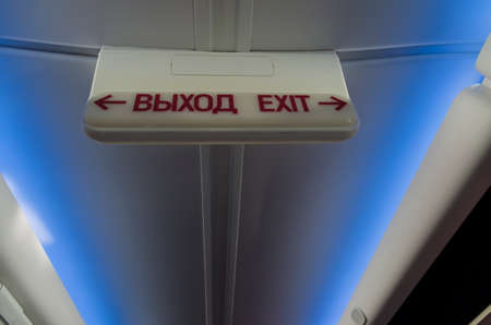 Information luminous sign exit in Russian and English in the plane on the background of the ceiling with a blue light