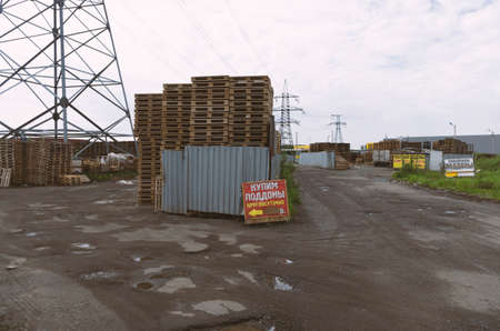 Saint Petersburg, Russia - June 7, 2020: Industrial area and pallet warehouse with posters in Russian 'buy pallets' in the background of high-voltage transmission lines Редакционное