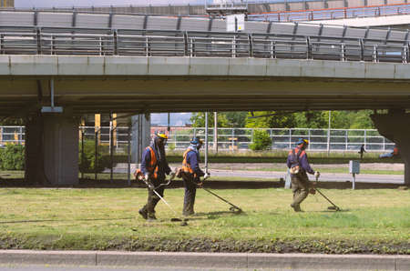 Saint Petersburg, Russia - July 26, 2020: Three workers with string trimmers in orange jumpsuits mow the grass near the highway