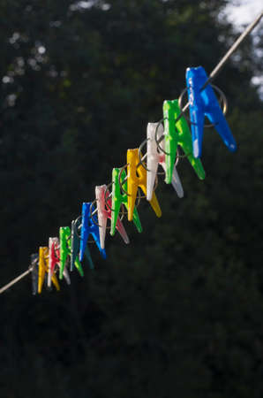 Row of colorful clothespins on a clothesline on a black background vertical orientation