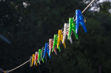 Row of colorful clothespins on a clothesline on a black background Фото со стока