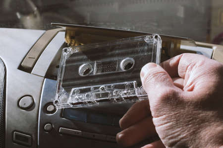 Audio tape is inserted into a stereo tape recorder with the widely used symbols without a trademark