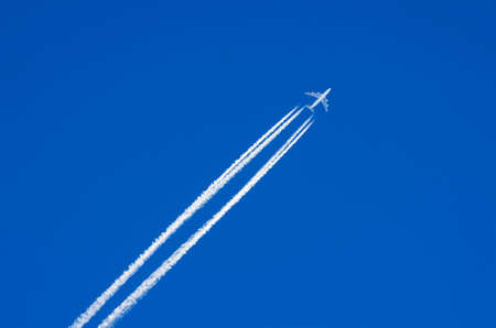 White airplane flies in the blue sky leaving a contrails behind it Reklamní fotografie