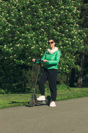 Young woman on an electric scooter on a bike path in a blooming city park Stockfoto