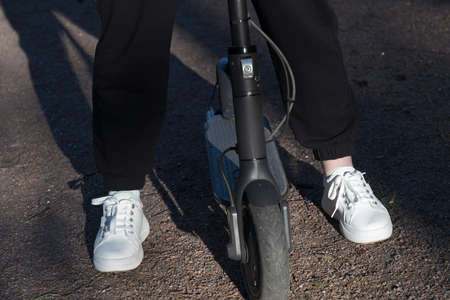 Young woman stands on a kick scooter in white sneakers and black pants in the profile Stockfoto