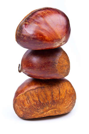 Three chestnuts put against each other on a white background